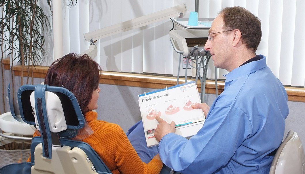 Dr. Sanker talking to patient in dental chair