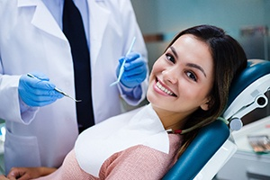 person smiling and looking over their shoulder while sitting in a dental treatment chair